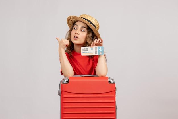 Вид спереди праздничной девушки с чемоданом, держащей билет, делая знак