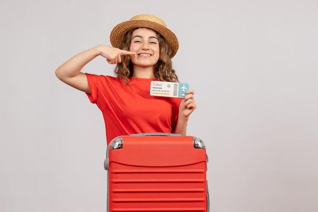 彼女の笑顔を指している彼女のスーツケース保持チケットと休日の女の子の正面図