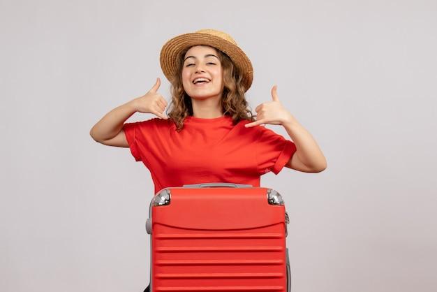 白い孤立した壁に立っているサインを私に電話をかける彼女のスーツケースを持つ休日の女の子の正面図