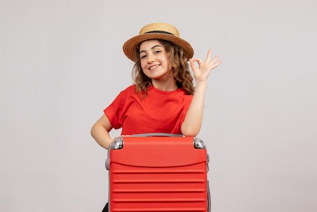 Праздничная девушка с чемоданом, делающая знак ок, стоя на белой стене, вид спереди