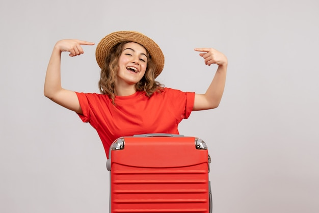 Вид спереди отпускной девушки с чемоданом, указывающей на ее панаму, стоящую на белой стене