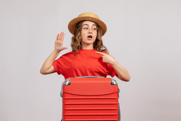 白い孤立した壁に立っている彼女のスーツケースと休日の女の子の正面図