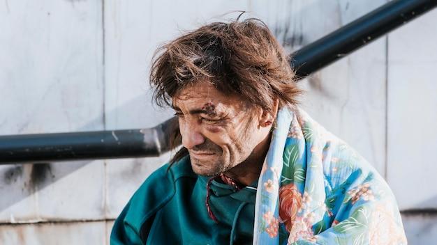 毛布で外のホームレスの男性の正面図