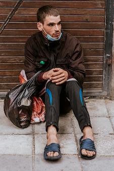 屋外でビニール袋を持つホームレスの男性の正面図