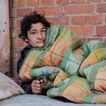 야외 담요 아래 노숙자 여자의 전면보기