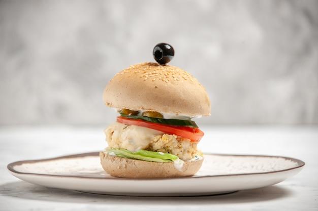 空きスペースのあるステンド グラスの白い表面のプレートに自家製のおいしいサンドイッチの正面図