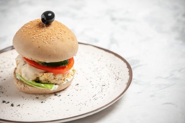 フリースペースのあるステンドグラスの表面にプレートにブラックオリーブを入れた自家製のおいしいサンドイッチの正面図
