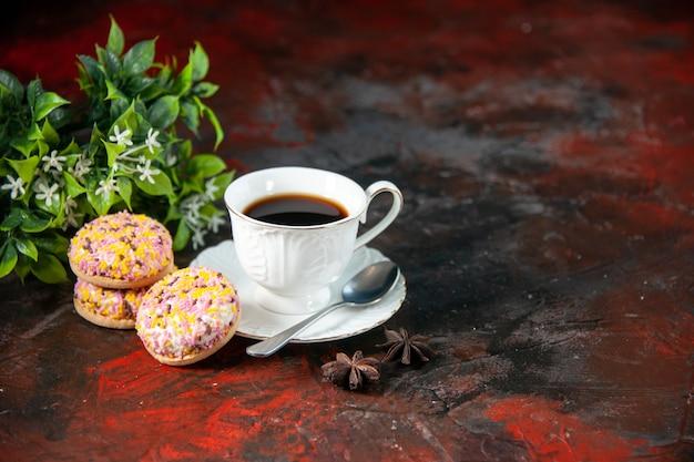 Вид спереди домашнего вкусного сахарного печенья и чашки кофейного цветочного горшка на фоне темных цветов со свободным пространством