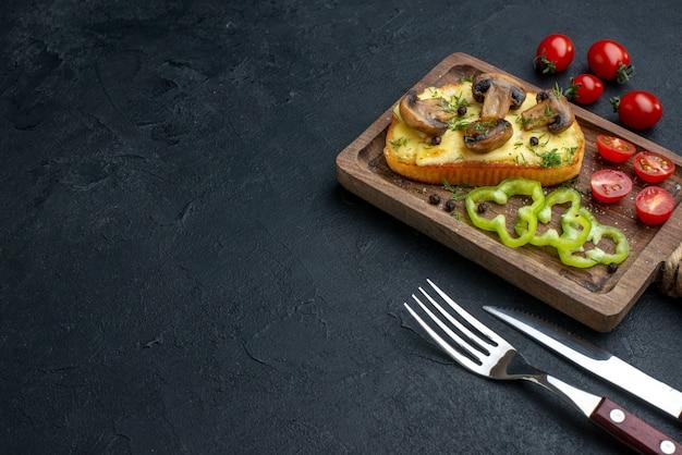 검은 배경에 놓인 나무 보드 칼에 버섯과 다진 야채를 곁들인 홈메이드 맛있는 스낵의 전면 전망