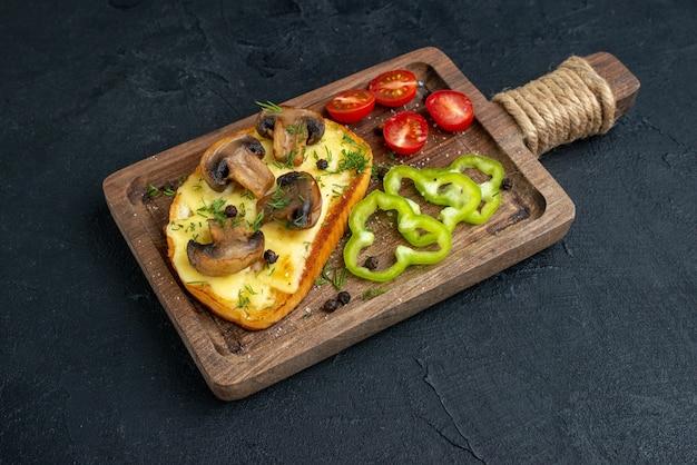 검은 배경에 나무 판자에 버섯과 다진 야채를 곁들인 홈메이드 맛있는 간식의 전면 전망