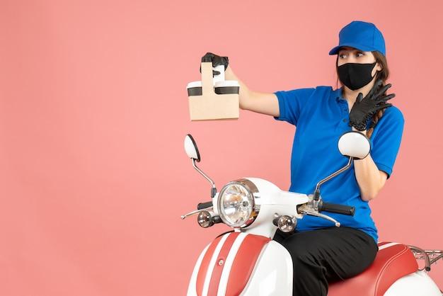 パステルピーチの背景に注文を保持しているスクーターに座っている医療用マスクと手袋を着た希望に満ちた女性配達員の正面図