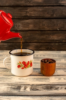 木製の机の上の赤いやかんから注ぐ熱いお茶の正面図