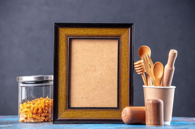 空の図枠内のさまざまなスパイス パスタをガラスの鍋に入れた正面図、青いテーブルに木のスプーン