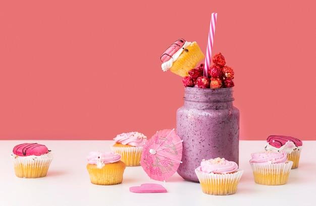 Вид спереди банку десерта с фруктами и кексы