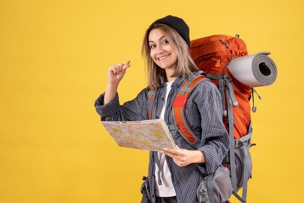 地図を保持しているバックパックとうれしそうな旅行者の女性の正面図