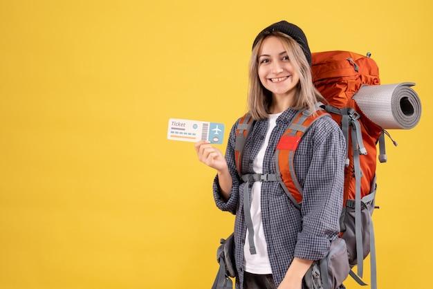 Вид спереди радостной женщины-путешественницы с рюкзаком, держащим билет
