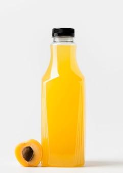 Вид спереди стеклянной бутылки сока с фруктами персика