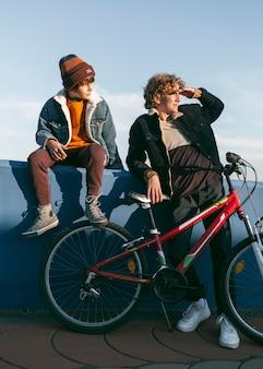 Вид спереди детей с велосипедом на открытом воздухе