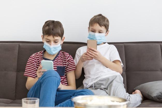 スマートフォンで遊ぶ医療用マスクを持つ子供の正面図