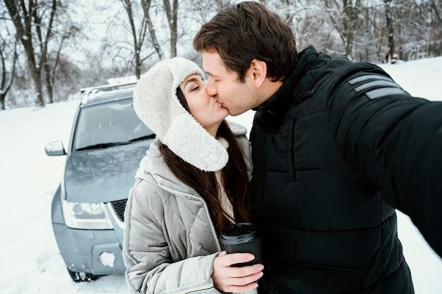 ロードトリップ中に自分撮りをしているカップルにキスをする正面図