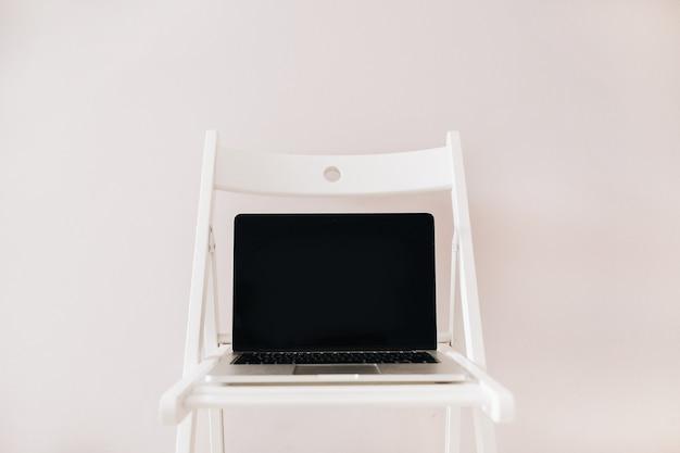 Вид спереди ноутбука с пустым макетом экрана рабочего стола на белом стуле