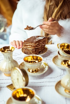 Вид спереди руки маленькой красивой девушки, держа кусок пирога на ложку в парке