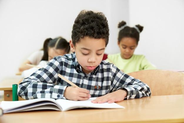 学校でテストを行っている途中の小さな男の子の正面図