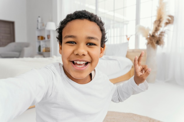 Маленький мальчик, делающий селфи дома, вид спереди