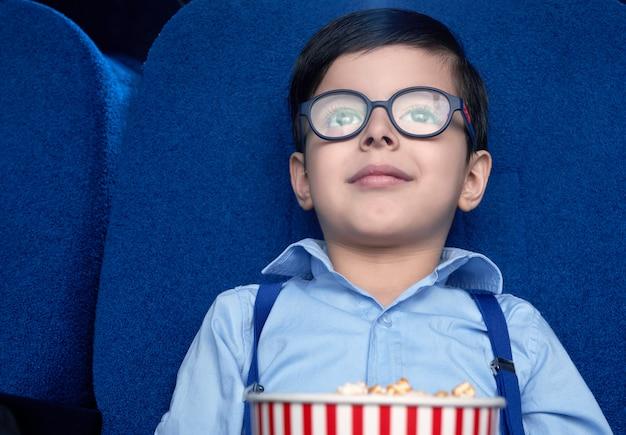 Вид спереди маленького мальчика, смотреть возбужденный фильм в кино