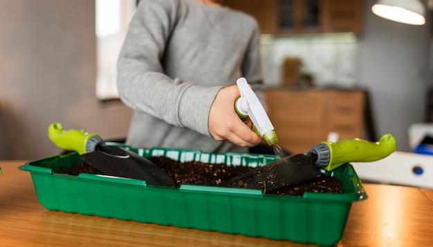 家で作物に水をまく少年の正面図