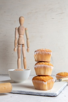 Вид спереди маленьких пирожных внутри бумажных форм с сахарной пудрой на белой поверхности