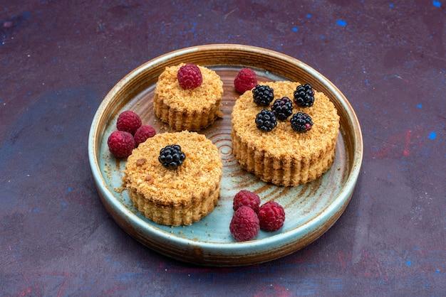 Вид спереди сладких и вкусных пирожных с ягодами на темной поверхности