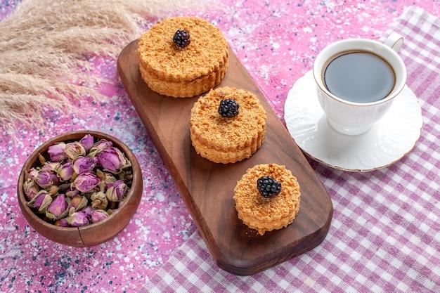 Вид спереди маленьких пирожных с чашкой чая на розовой поверхности