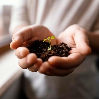Вид спереди маленького ребенка, держащего в руках грязь и ростки