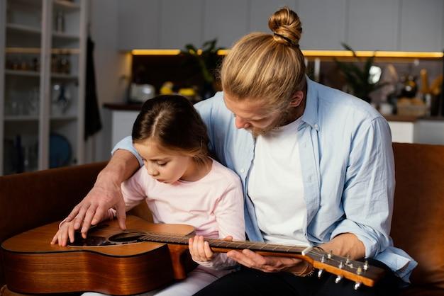 一緒にギターを弾く少女と父親の正面図