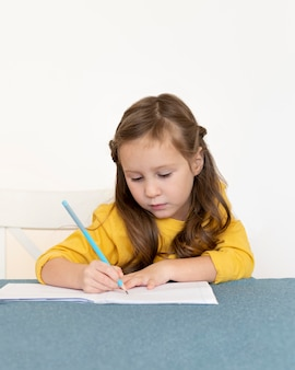 Маленькая девочка делает домашнее задание, вид спереди