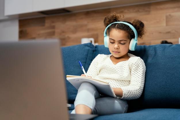 노트북 및 헤드폰 온라인 학교 동안 어린 소녀의 전면보기