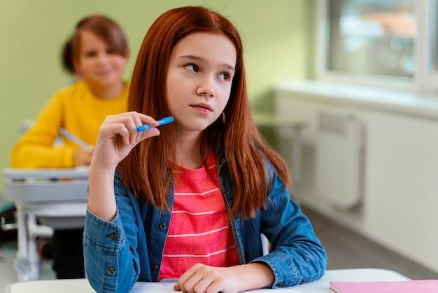 Вид спереди маленькой девочки в классе в школе