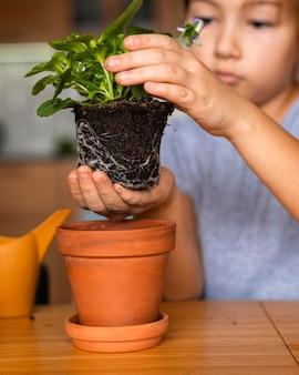 집에서 냄비에 꽃을 심는 어린 소녀의 전면보기