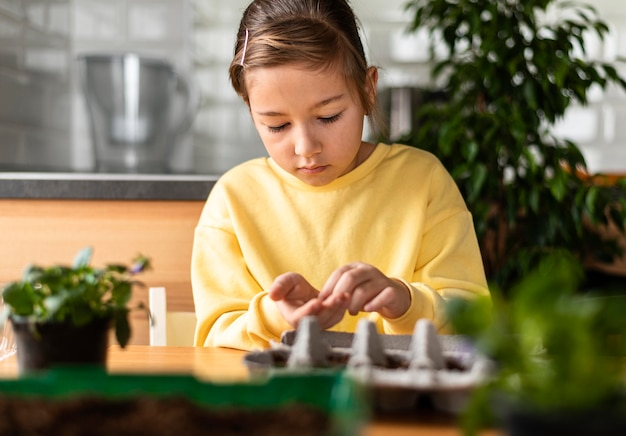 Маленькая девочка сажает семена дома, вид спереди
