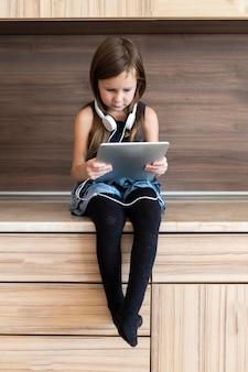 Вид спереди маленькой девочки с помощью планшета с наушниками