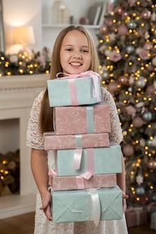Вид спереди маленькой девочки с рождественскими подарками