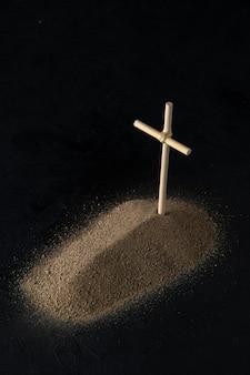 Вид спереди могилы из песка с палкой крест на черном