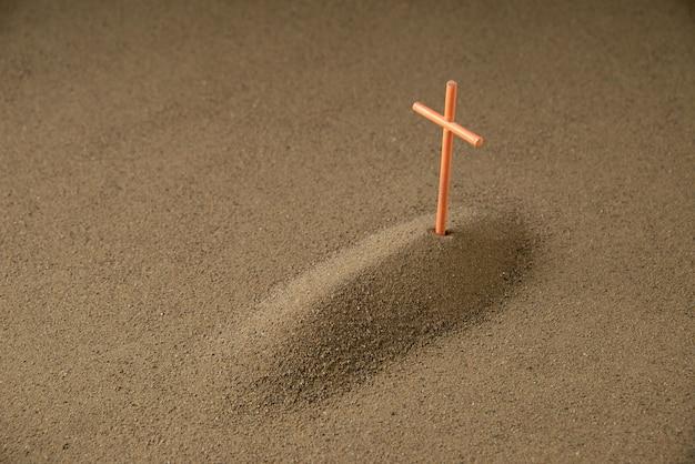 Вид спереди могилы с крестом на темноте