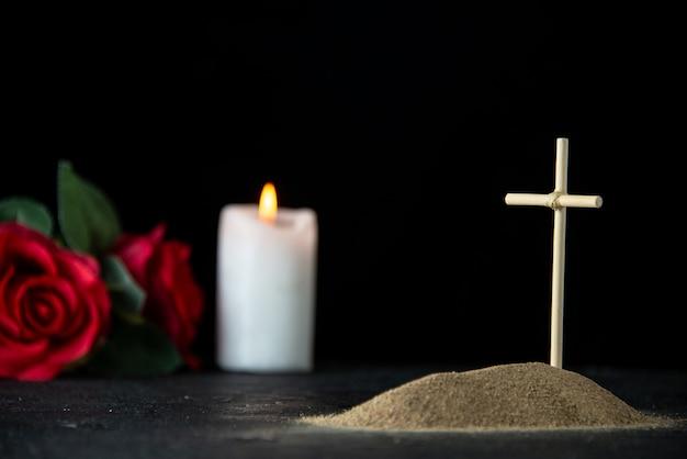 어둠에 꽃과 촛불 작은 무덤의 전면보기