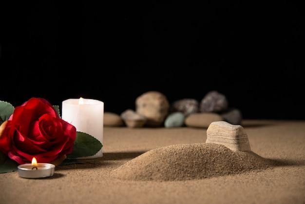 모래 장례식 죽음에 붉은 꽃과 촛불이있는 작은 무덤의 전면보기