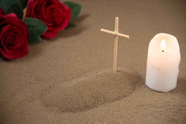붉은 꽃과 촛불 작은 무덤의 전면보기