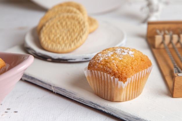 砂糖粉末と白い机の上のクッキーと小さなおいしいケーキの正面図