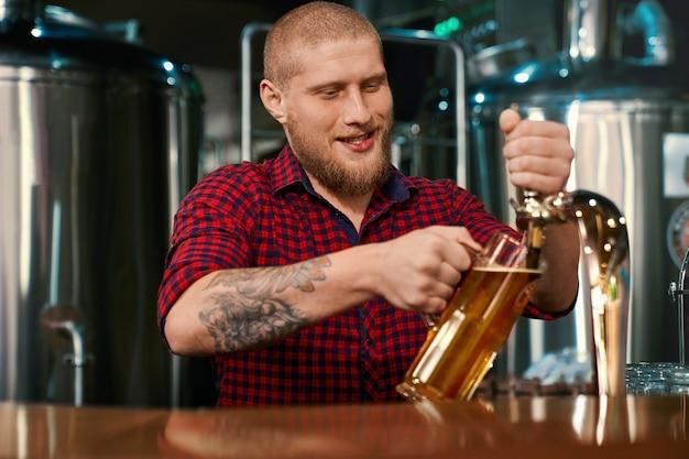 술집에서 일하고 유리에 맥주를 붓는 남성 barmen의 전면 모습. 양조장에서 사람들을 서비스하는 젊은 수염 남자. 카운터에 서있는 남성, 웃음과 이야기. 음료의 개념.