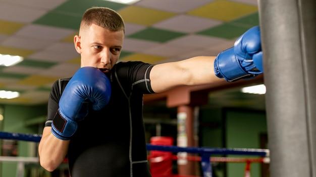 リングでトレーニングしている手袋をした男性ボクサーの正面図